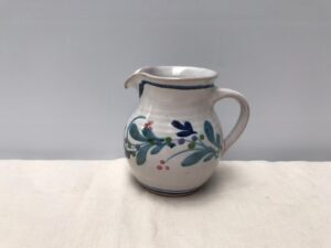 Side view of a small rounded cream jug by Nicola Werner painted with Mistletoe pattern mostly in blue and bluegreen,